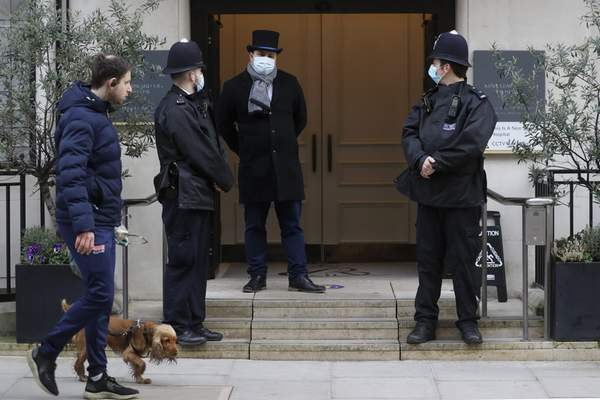 A man walks by with a dog as police officers stand outside King Edward VII's hospital in London, Tuesday, Feb. 23, 2021. (AP Photo/Kirsty Wigglesworth)