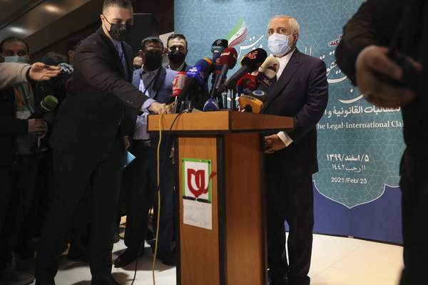 Iran's Foreign Minister Mohammad Javad Zarif prepares to speak with journalists following a conference in Tehran, Iran, Tuesday, Feb. 23, 2021. Iran's foreign minister says the country has started implementing a law passed by the parliament to curb UN inspections into its nuclear program. Zarif reiterated that Iran would no longer share surveillance footage of its nuclear facilities with the U.N. agency. (AP Photo/Vahid Salemi)