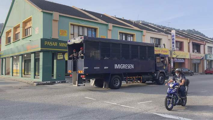 In this image taken from a video, an immigration truck with security and unidentified people drives on a road that leads to Lumut Naval Base Tuesday, Feb. 23, 2021 in Lumut, Malaysia. (AP Photo)