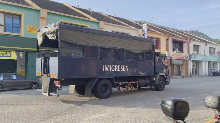 In this image taken from a video, an immigration truck with unidentified people onboard is driven on a road that leads to Lumut Naval Base Tuesday, Feb. 23, 2021 in Lumut, Malaysia. (AP Photo)