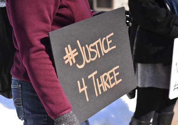 "A person holds a sign reading ""#Justice4Three"" at Tuesday's rally in the aftermath of the shooting deaths of Anderson Retic and Joshua Cole Cooper, both 19, and the wounding of Jaylin Rice, 20."