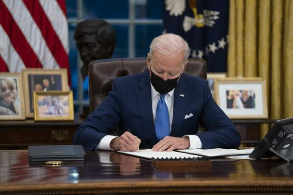 FILE - In this Feb. 2, 2021, file photo, President Joe Biden signs an executive order, in the Oval Office of the White House, in Washington. (AP Photo/Evan Vucci, File)
