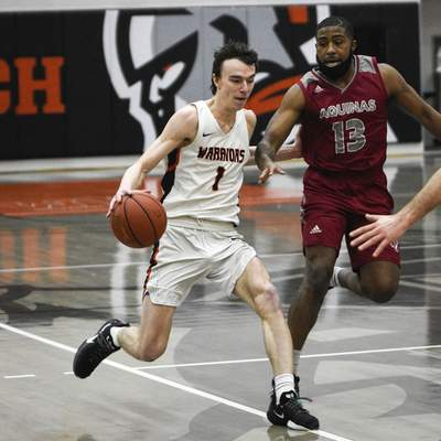 Mike Moore | The Journal Gazette Indiana Tech guard Grant Smith controls the ball in the first half against Aquinas at the Schaefer Center on Thursday.
