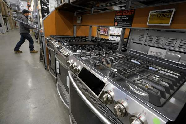 This Oct. 29, 2020 file photo, a passer-by walks past stoves on display at a Home Depot location, in Boston. (AP Photo/Steven Senne, File)