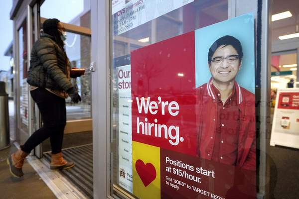 FILE - In this Feb. 9, 2021 file photo, a passer-by walks past an employment hiring sign while entering a Target store location, in Westwood, Mass. (AP Photo/Steven Senne, File)