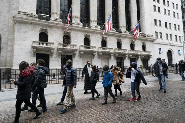 A school group walks by the New York Stock Exchange, Tuesday, Feb. 23, 2021. (AP Photo/Mark Lennihan)