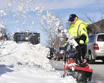 Katie Fyfe | The Journal Gazette Scott Jewell with Parks and Recreation clears away snow at Promenade Park on Thursday afternoon.