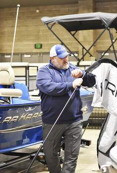 Katie Fyfe | The Journal Gazette Ryan Coverstone with Socks Marina sets up Thursday for the All-American Outdoor Expo, which runs from today through Sunday at Memorial Coliseum.