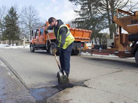 Michelle Davies | The Journal Gazette Shawn Rogers with the Fort Wayne Street Department fills potholes Friday afternoon along Copper Hill Run.