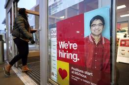Federal Reserve Associated Press  In this Feb. 9, 2021, file photo, a passer-by walks past an employment hiring sign while entering a Target store location in Westwood, Mass. (Steven SenneSTF)
