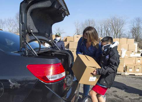 Photos by Michelle Davies | The Journal Gazette Elizabeth Thongkoth, of Fort Wayne, helps her son Paxton, 10, load a box of food into a car during Saturday's food distribution at the  Buddha Temple Worship Center of Decatur Road.