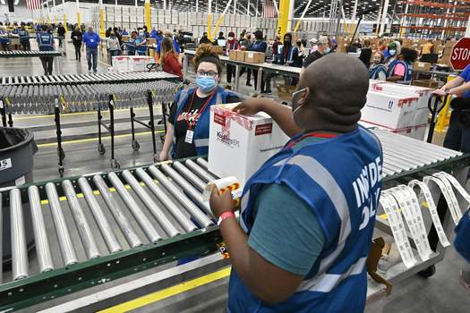 APTOPIX Virus Outbreak Vaccine Associated Press  The first box containing the Johnson & Johnson COVID-19 vaccine heads down the conveyor to an awaiting transport truck Monday at the McKesson facility in Shepherdsville, Ky. (Timothy D. EasleyPOOL)