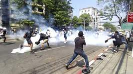 APTOPIX Myanmar Associated Press In this image from a video, anti-coup protesters run away from tear gas launched by security forces Monday in Yangon, Myanmar. (TEL)