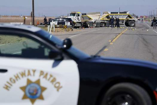 California Highway Crash Law enforcement officers work at the scene of a deadly crash in Holtville, Calif., on Tuesday, March 2, 2021. Authorities say a semi-truck crashed into an SUV carrying 25 people on a Southern California highway, killing at least 13 people. (AP Photo/Gregory Bull) (Gregory Bull STF)
