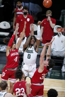 Associated Press Aaron Henry shoots between Khristian Lander, left, and Trey Galloway on Tuesday night in East Lansing, Mich.
