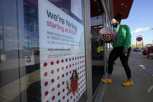 Virus Outbreak Unemployment Benefits FILE - In this Sept. 30, 2020, file photo, a passerby walks past a hiring sign while entering a Target store in Westwood, Mass. The number of Americans applying for unemployment benefits edged higher last week to 745,000, a sign that many employers continue to cut jobs despite a drop in confirmed viral infections and evidence that the overall economy is improving. (AP Photo/Steven Senne, File) (Steven Senne STF)
