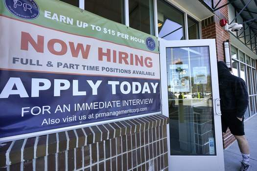 """Virus Outbreak Employment Associated Press A man walks into a restaurant displaying a """"Now Hiring"""" sign Thursday in Salem, N.H. (Elise AmendolaSTF)"""