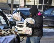 Mike Moore   The Journal Gazette A staff members at North Side High School passes out meals last month.
