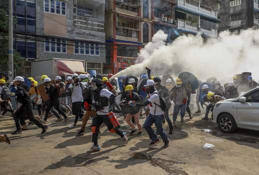 Myanmar Sanctions FILE - In this March 3, 2021, file photo, anti-coup protesters run as one of them discharges a fire extinguisher to counter the impact of tear gas fired by riot policemen in Yangon, Myanmar. (AP Photo/File) (STR STR)
