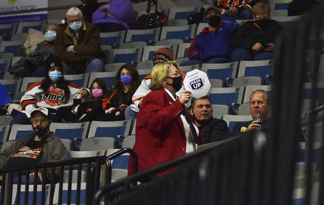 Memorial Coliseum ushers, wearing red coats, remind fans at Komets games to keep their masks on.