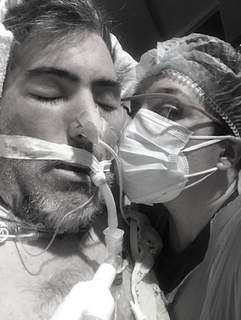 Courtesy Melissa Shanks, right, takes a selfie while kissing husband Jason Shanks, who was sedated and intubated for six weeks after his COVID-19 diagnosis last year.