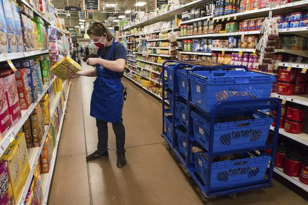 Michelle Davies   The Journal Gazette Jacob Mertz, ecommerce clerk for Kroger, scans items to be added to curbside pickup orders.