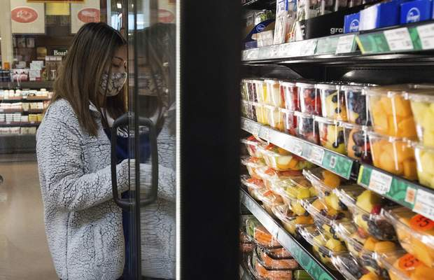 Michelle Davies   The Journal Gazette Jessica Cozatl, ecommerce clerk for Kroger, picks out items for a curbside grocery order.