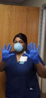 Courtesy Sherrell Mims, a registered nurse, shows off a message on her gloves informing people how to avoid contracting the novel coronavirus.