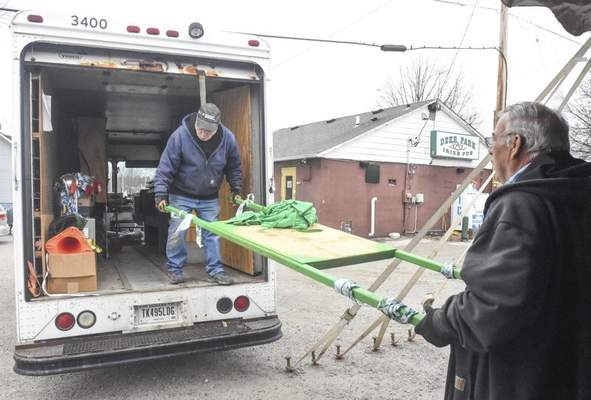 Michelle Davies   The Journal Gazette Part-time workers Jim Orth, left, of New Haven and Russell Wallace of Andrews load a float that would have been used to carry a statue of St. Patrick in what would have been Deer Park Irish Pub's 22nd annual Clover Classic. Tony Henry, owner of Deer Park, has made the decisiion to cancel the festivities to protect the people that would have attended the event from the spread of the coronavirus outbreak.