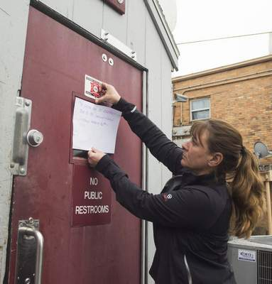 Michelle Davies   The Journal Gazette Gina Fey, part of the wait staff at Oyster Bar, hangs a closure notice sign on the back door of the Calhoun Street restaurant.