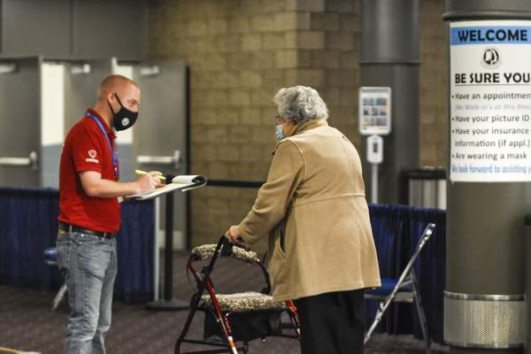 Mike Moore | The Journal Gazette A member of the Allen County Department of Health checks in a patient to receive the COVID-19 vaccination at  Memorial Coliseum, which opened for residents to get the vaccine Jan. 12.