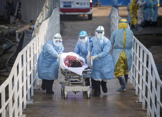 Associated Press Workers transfer patients into the quickly completed Huoshenshan field hospital in Wuham, China, in early February 2020.