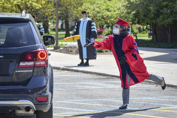 Mike Moore | The Journal Gazette Isabel Nunez, Purdue University Fort Wayne director of the school of education, tosses a T-shirt to a graduating student as the student drives through the campus to be recognized for her accomplishment.