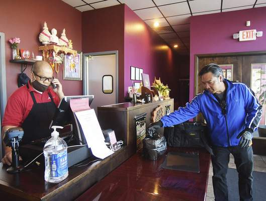 Katie Fyfe | The Journal Gazette  Pete Rugsaken, owner of the restaurant Baan Thai, takes orders over the phone while Nick Suth with Waiter on the Way packs up carry outs on Wednesday, May 6th, 2020.