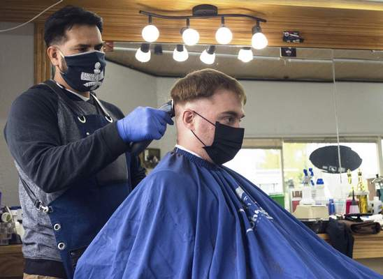 Michelle Davies | The Journal Gazette Father Jay Horning gets a haircut Monday morning from his favorite barber, Jose Martinez, at Barbers United Barber Shop on South Wayne Avenue.