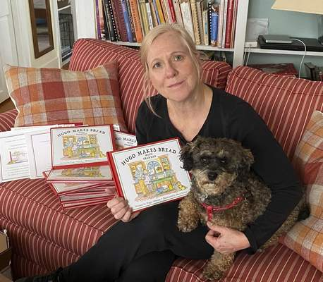 """Courtesy photos Peggy Alberda sits with Lulu, herHaverpoo dog, who sneaks onto the pages of her book, """"Hugo Makes Bread with Grandad."""""""