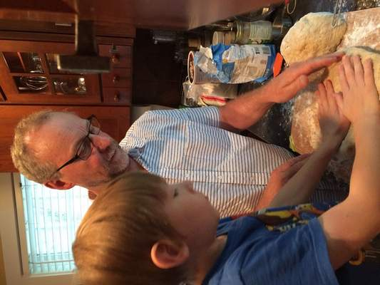 Granddad, Peggy Alberda's husband, works with a young Asa to make bread.