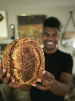 Associated Press Broadway performer Max Kumangai holds a loaf of sourdough bread at his apartment in New York. He has sold bread through his company Humpday Dough during the pandemic.