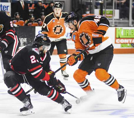 Katie Fyfe | The Journal Gazette  Komets' Zach Pochiro carries the puck while Indy Fuel defenseman tries to block him during the second period at Memorial Coliseum on Friday.