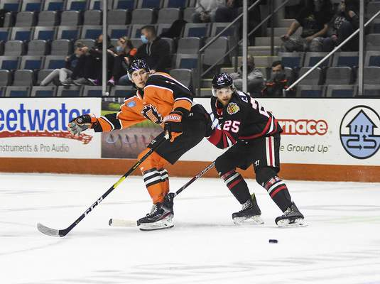 Katie Fyfe | The Journal Gazette  Komets forward Jason Cotton and Indy Fuel defenseman Cliff Watson chase after the puck during the first period at Memorial Coliseum on Friday.