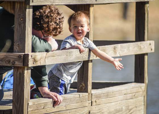 Mike Moore | The Journal Gazette  Daniel Grannis, 2, scouts for fish Saturday while enjoying the sunshine at Lakeside Park with his father Logan Grannis.