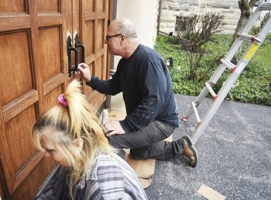 Katie Fyfe | The Journal Gazette  Jeannie Potter and Thomas Kindschy stain the doors outside a historic property on Wayne Street Thursday afternoon.