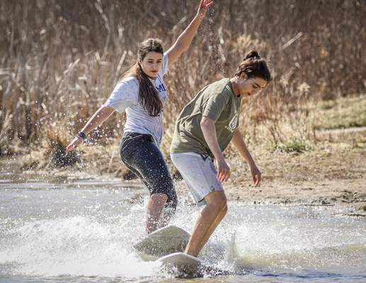 Mike Moore | The Journal Gazette  Siblings Evalyn Bellotti, 16, left, and Asher Bellotti, 14, make waves Sunday while skimboarding the chilly waters at Metea County Park in Leo-Cedarville.