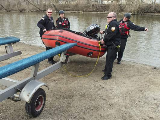 Michelle Davies | The Journal Gazette  Firefighters from Station 4 load a boat after performing routine water operations Thursday morning on the St. Joseph River.