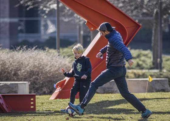 Mike Moore | The Journal Gazette  Foster Heath, 9, hones his soccer skills Saturday while practicing at Freimann Square downtown with his father Ryan Heath.
