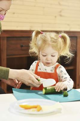Katie Fyfe | The Journal Gazette  Stella Kahlenbeck makes a leprechaun hat out of healthy foods during the St. Patty's Day Kids Cooking Class hosted by Wholesome Roots Cooking at Salamon Farm Park Tuesday morning.