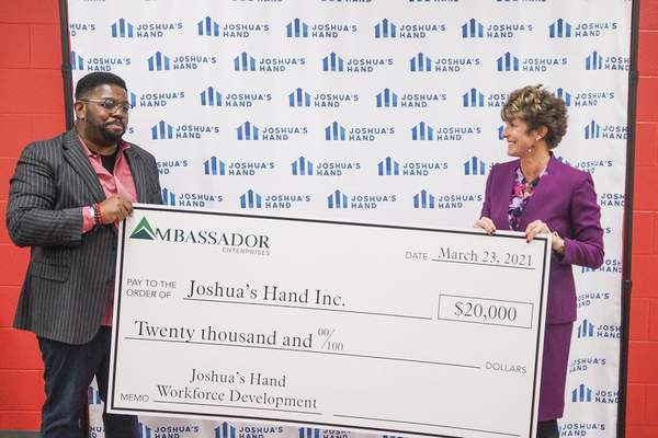 Mike Moore | The Journal Gazette  Sherry Grate, right, with Ambassador Enterprises, presents a check to Cedric Walker of Joshua's Hand Tuesday during a news conference at the McMillen Park Community Center.