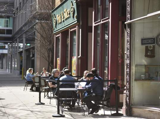 Katie Fyfe | The Journal Gazette  People enjoy dining outside Pint & Slice and Dash-In Monday afternoon.