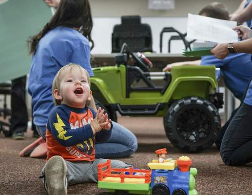 Mike Moore | The Journal Gazette  Landon Jones, 1, plays on the floor Saturday while caregivers build his new custom electric vehicle in the background during the GoBabyGo campaign for disabled children at Huntington University Occupational Therapy on Carew Street.