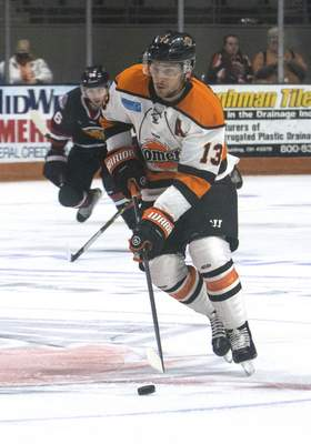 Michelle Davies | The Journal Gazette  Komets forward Anthony Petruzzelli brings the puck down the ice in the first period of Sunday's game against Indy Fuel at Memorial Coliseum.